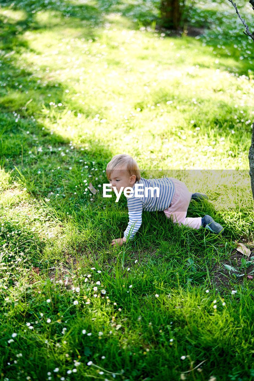 BOY STANDING BY GRASS