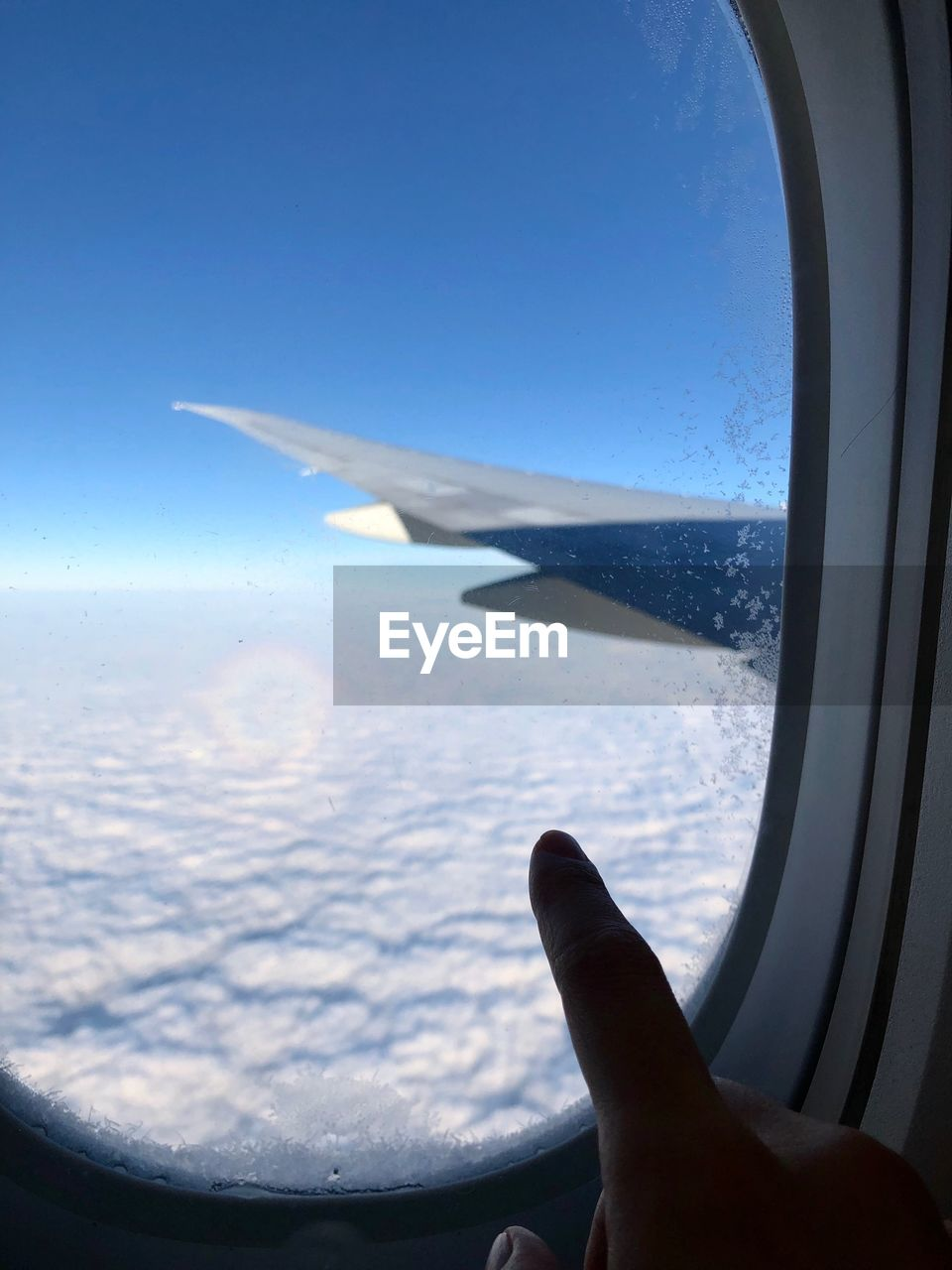 air vehicle, airplane, transportation, mode of transportation, sky, flying, window, glass - material, transparent, vehicle interior, human body part, travel, human hand, journey, mid-air, hand, aircraft wing, one person, blue, motion, body part, finger, outdoors