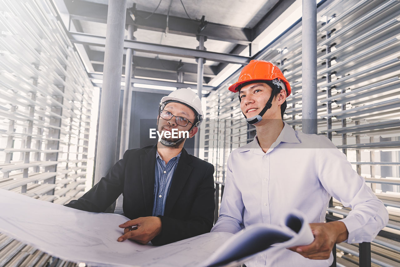 business, males, headwear, occupation, helmet, men, cooperation, real people, two people, young men, adult, businessman, hardhat, teamwork, indoors, young adult, business person, waist up, hat, coworker, mature men, design professional, blueprint, architect