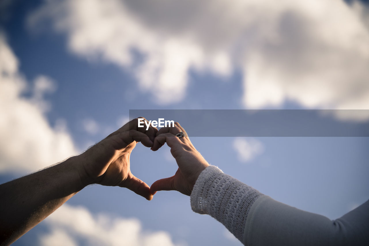 Cropped hands of couple making heart shape against blue sky