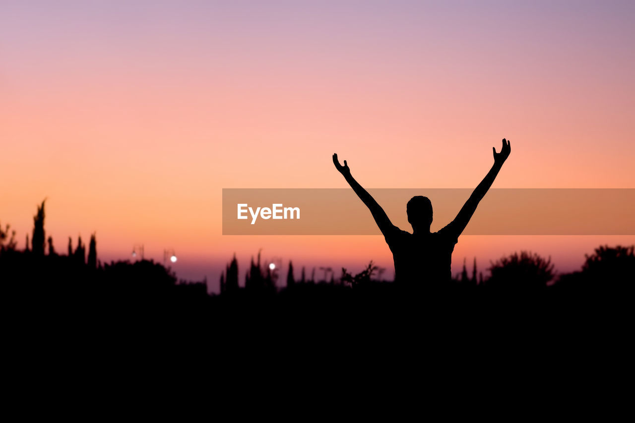 Silhouette man with arms raised standing against clear sky during sunset