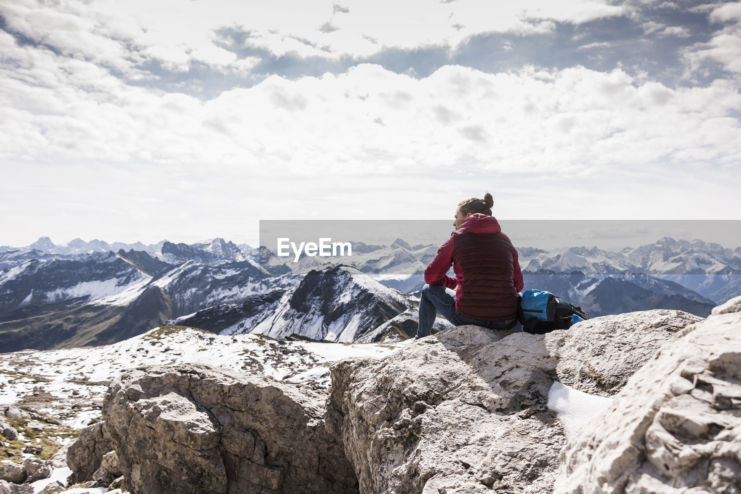 REAR VIEW OF MAN SITTING ON ROCK AGAINST SNOWCAPPED MOUNTAINS