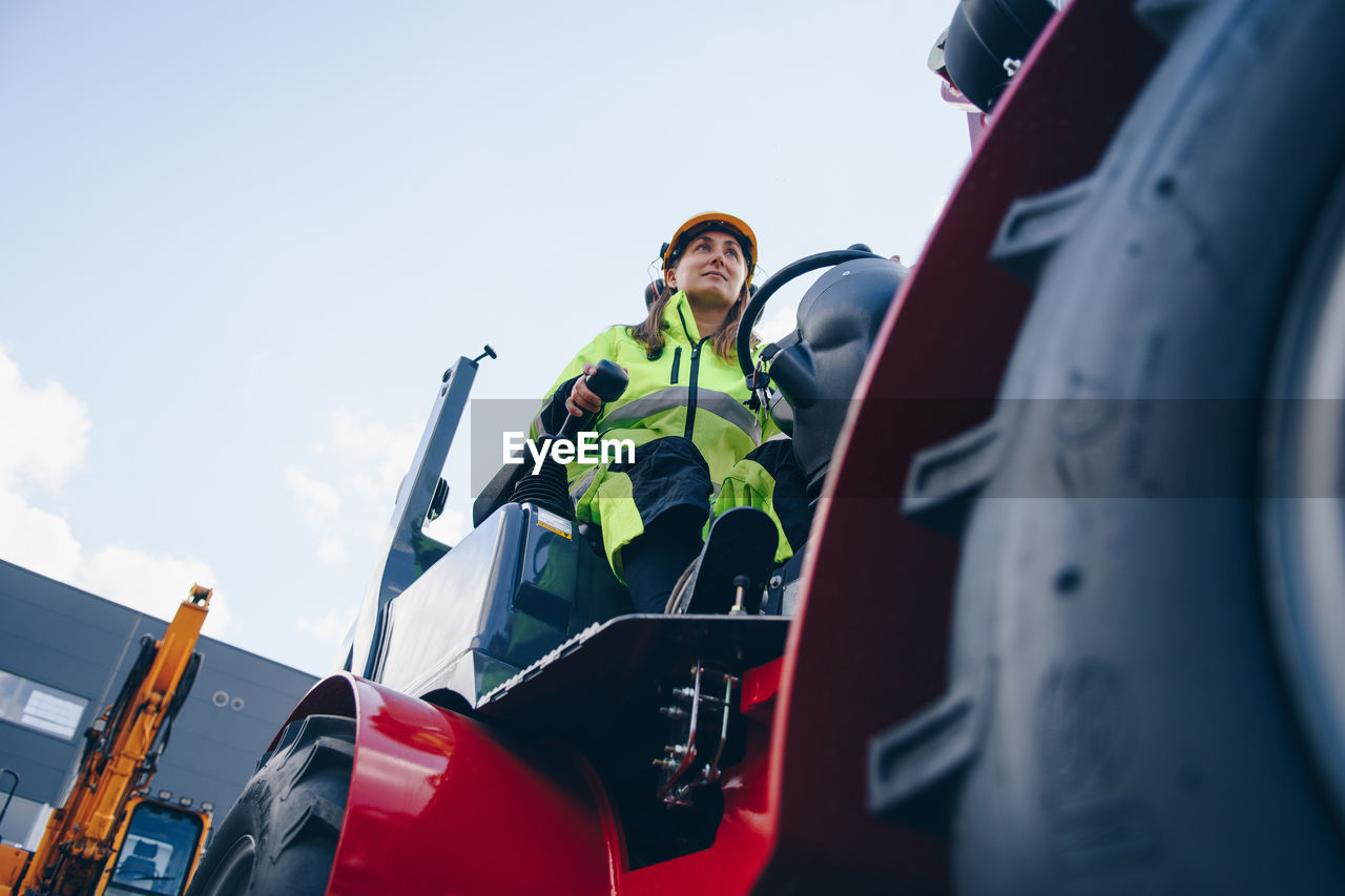 Woman Driving Construction Vehicle Against Sky