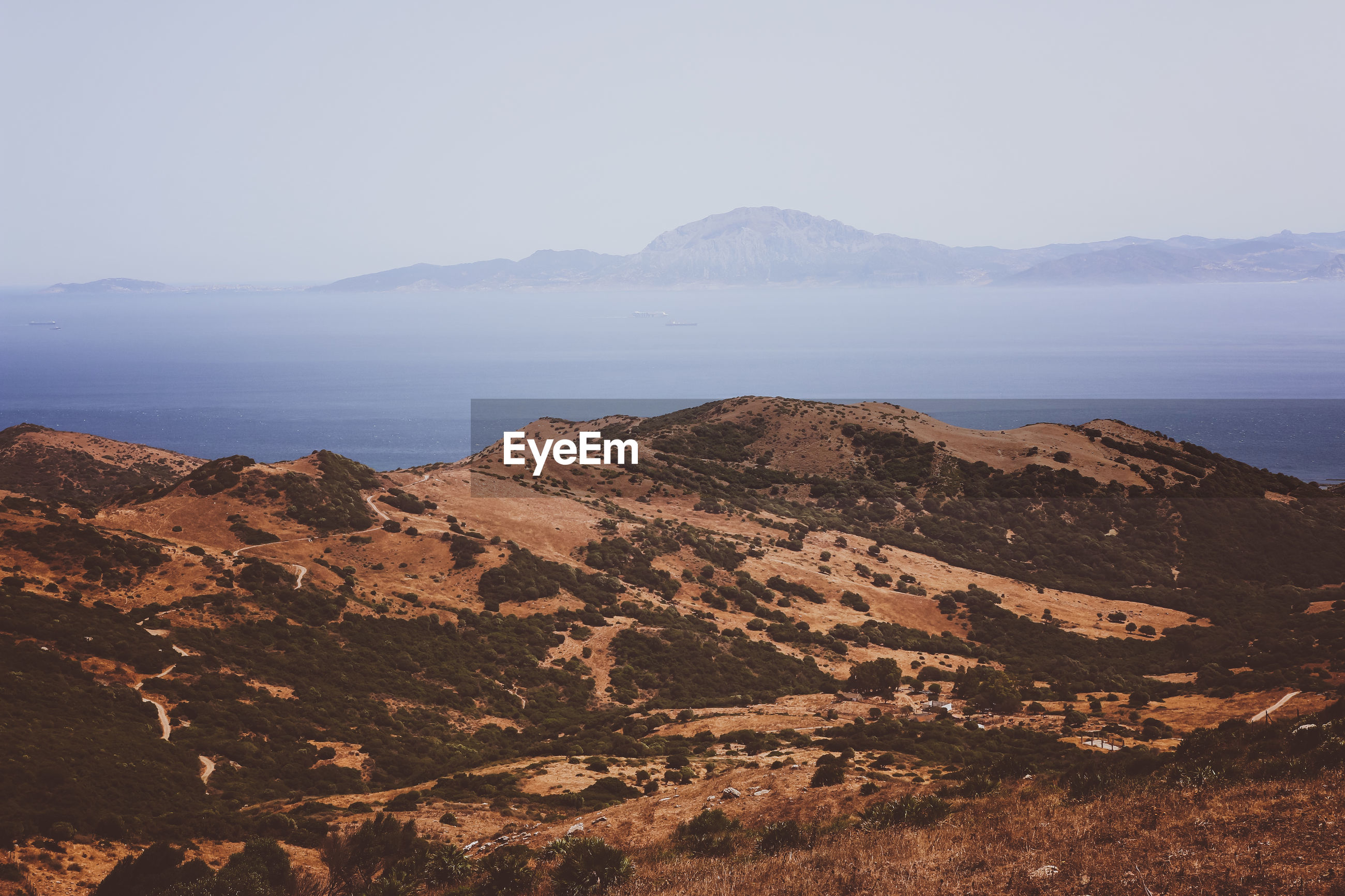SCENIC VIEW OF SEA BY MOUNTAINS AGAINST CLEAR SKY