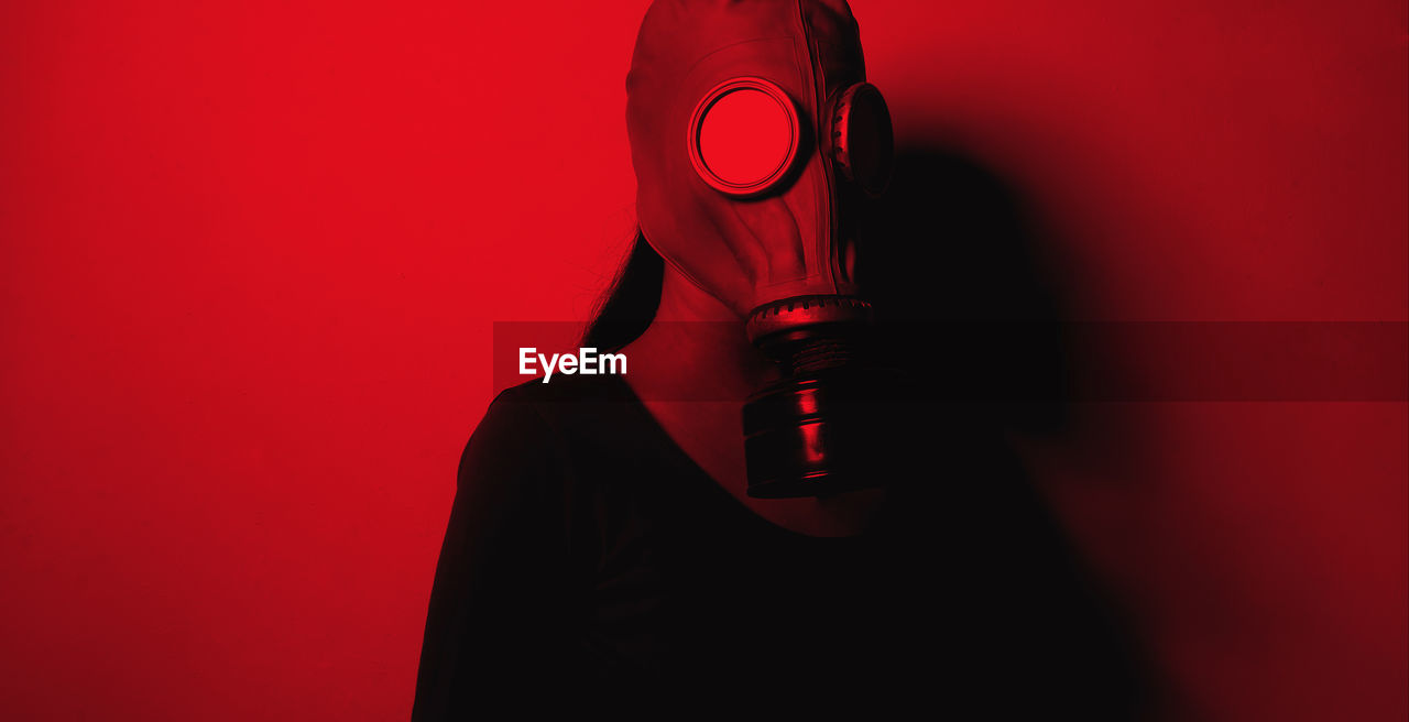 Woman Wearing Gas Mask Against Wall In Illuminated Room