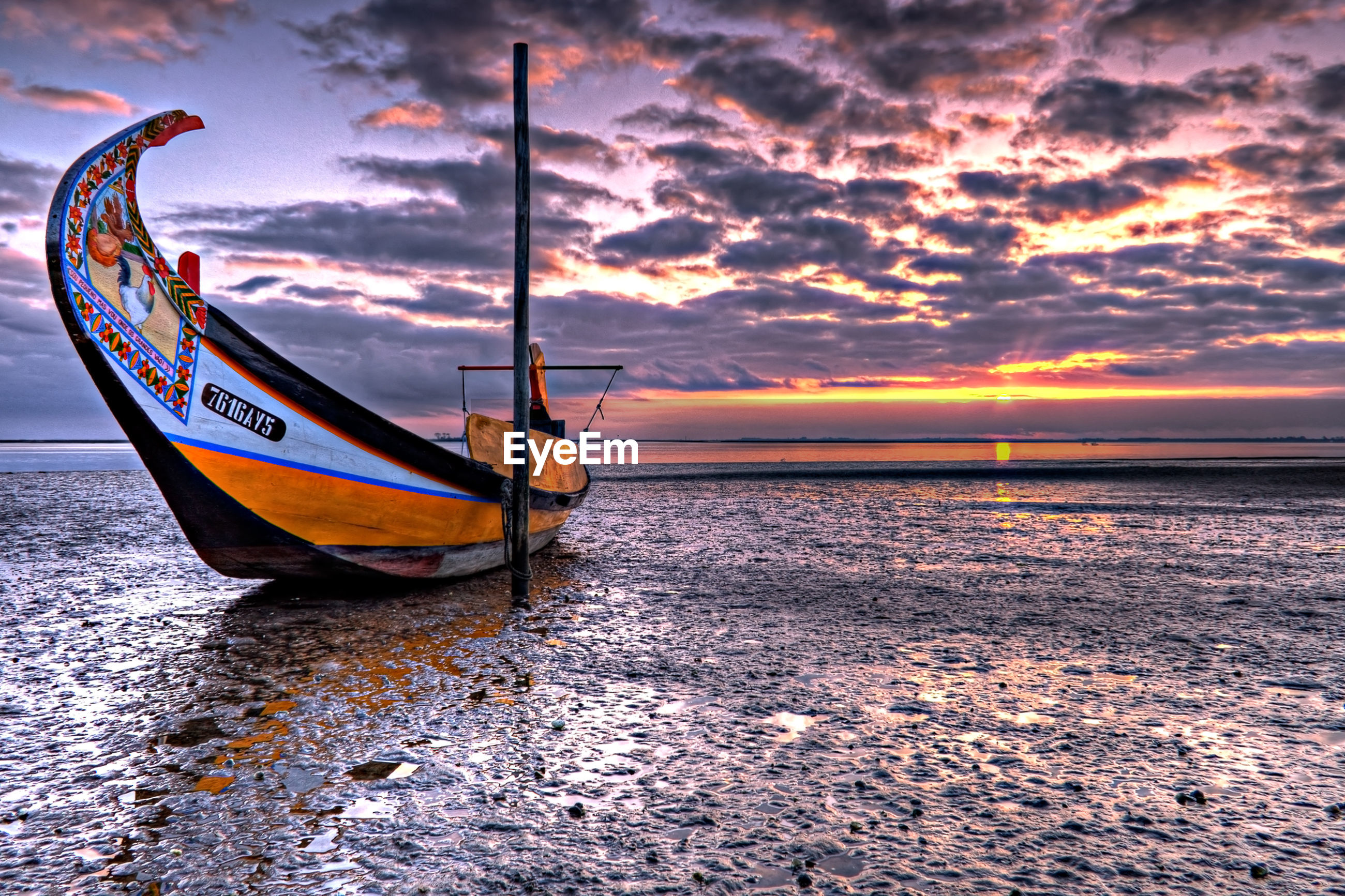 Fishing boat moored on shore at beach against cloudy sky during low tide