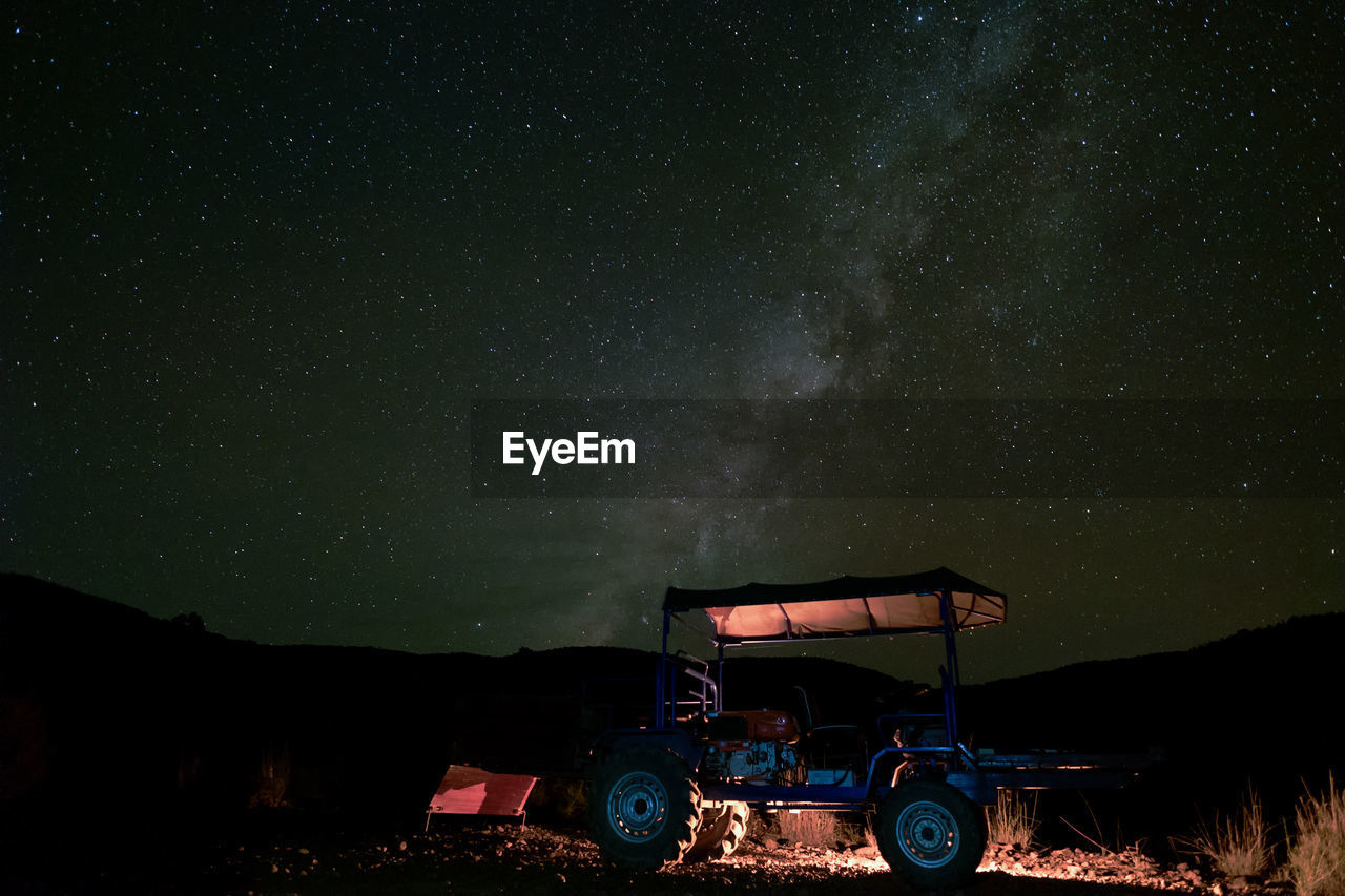 Cars on field against sky at night