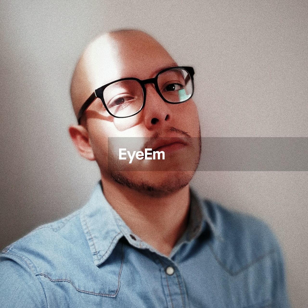 Close-Up Portrait Of Man Wearing Eyeglasses Against Wall