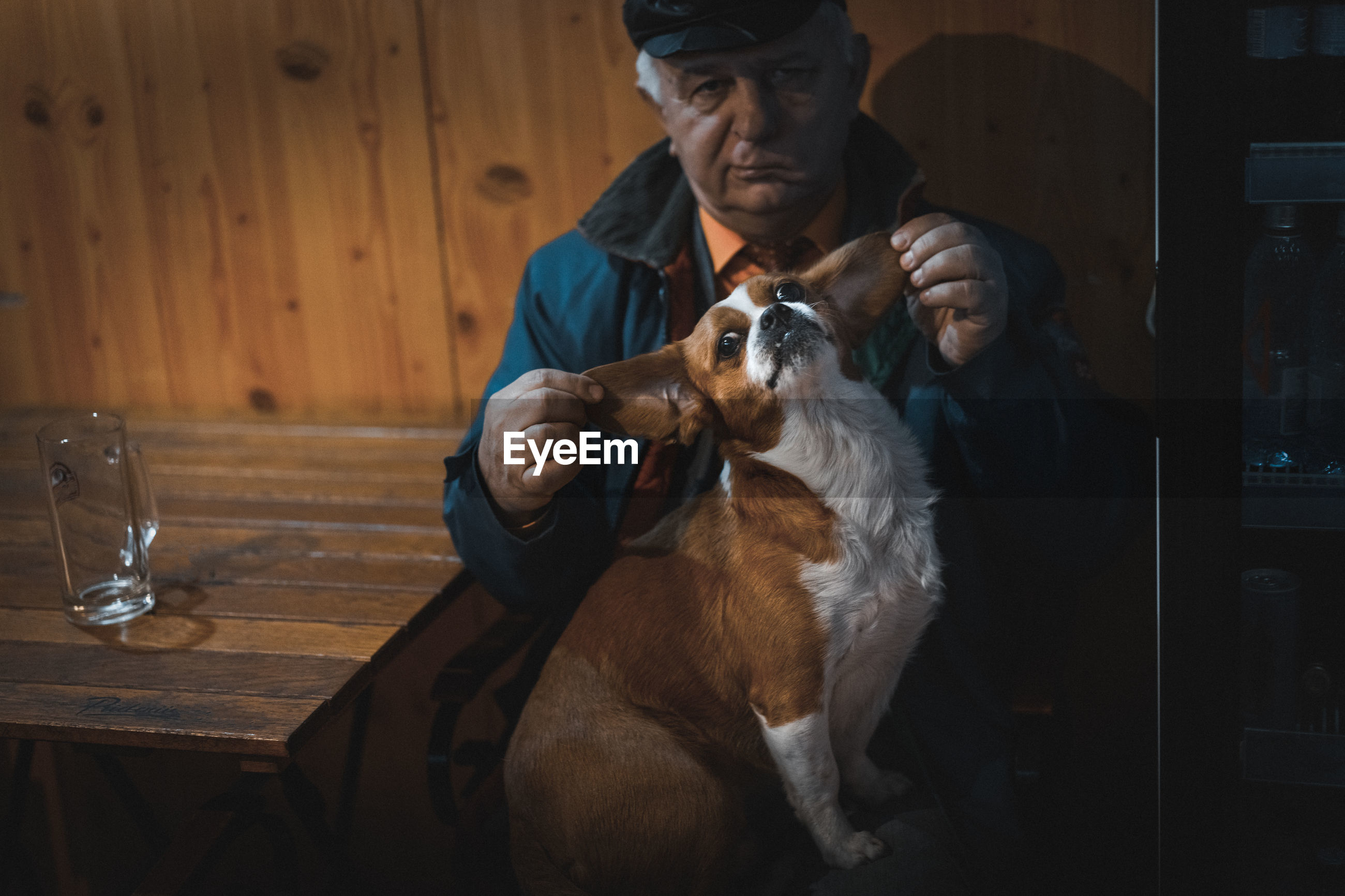 Close-up portrait of man with dog sitting on table