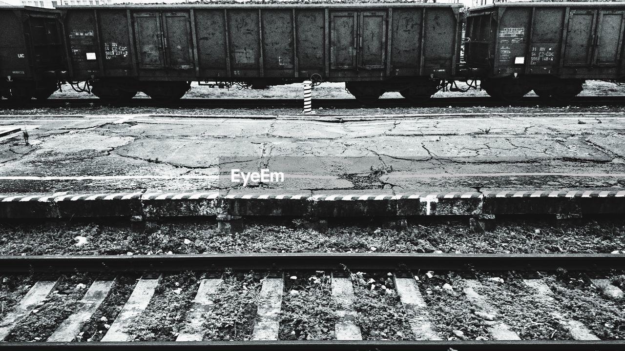 railroad track, rail transportation, transportation, railway track, day, outdoors, railroad station platform, railroad tie, sunlight, no people, train station, architecture