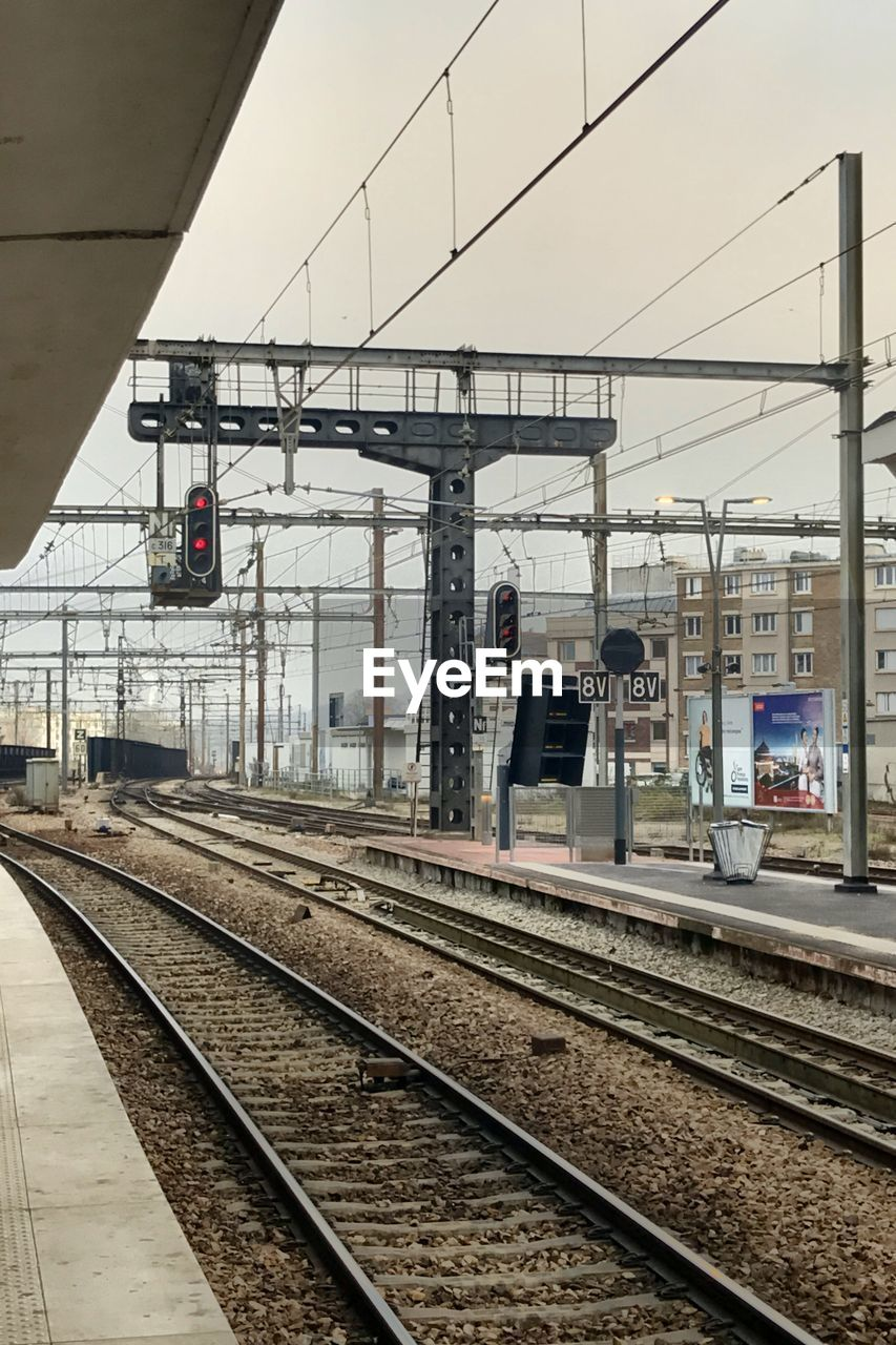 rail transportation, track, transportation, railroad track, mode of transportation, public transportation, sky, cable, railroad station, railroad station platform, train, nature, electricity, architecture, power line, outdoors, built structure, train - vehicle, day, no people, power supply, waiting