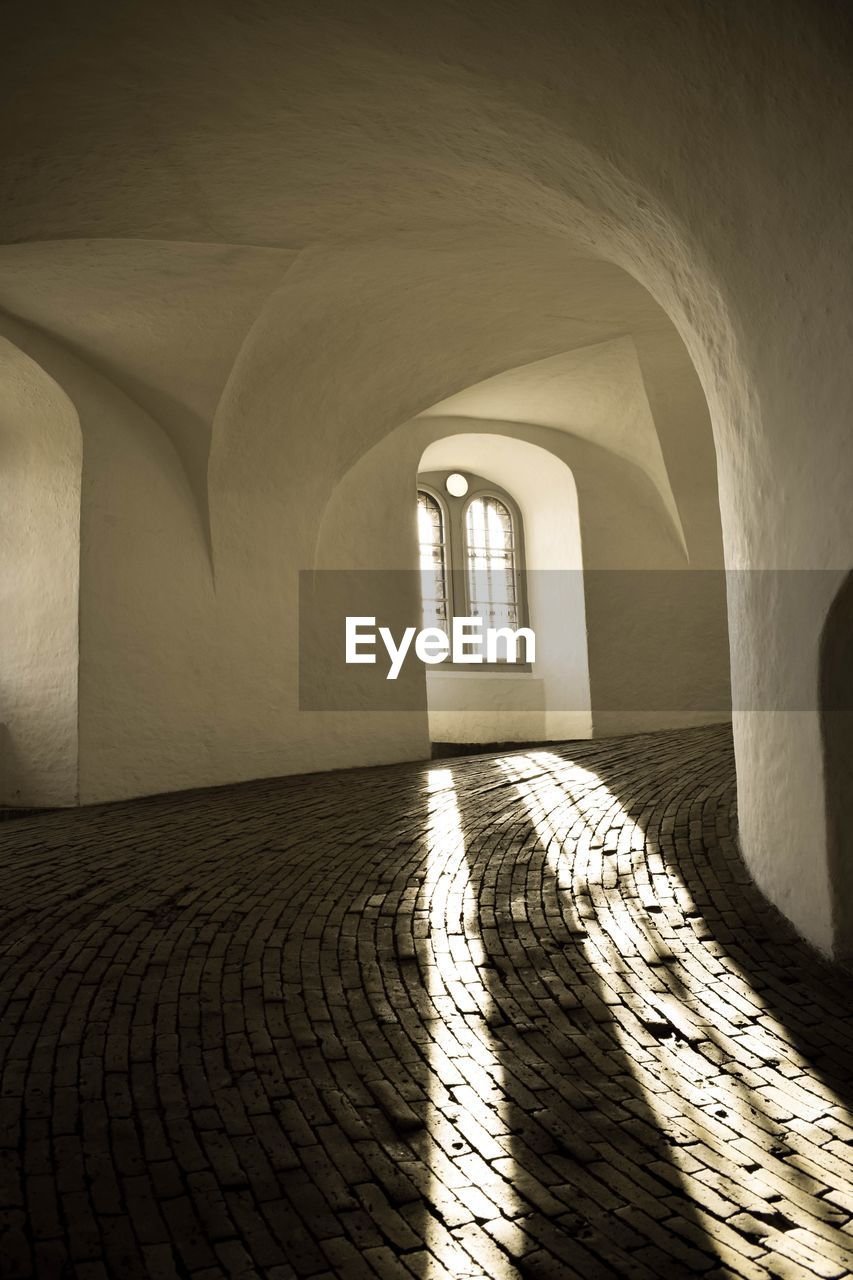 architecture, arch, built structure, the past, building, history, no people, indoors, sunlight, day, empty, the way forward, direction, cobblestone, travel destinations, arcade, wall, wall - building feature, absence, flooring, arched, architectural column