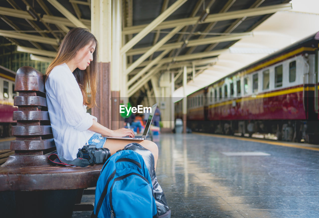 Side view of young woman using laptop while sitting on bench at railroad station