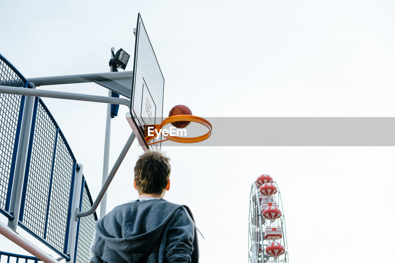 Rear View Of Man Playing Basketball On Court Against Clear Sky