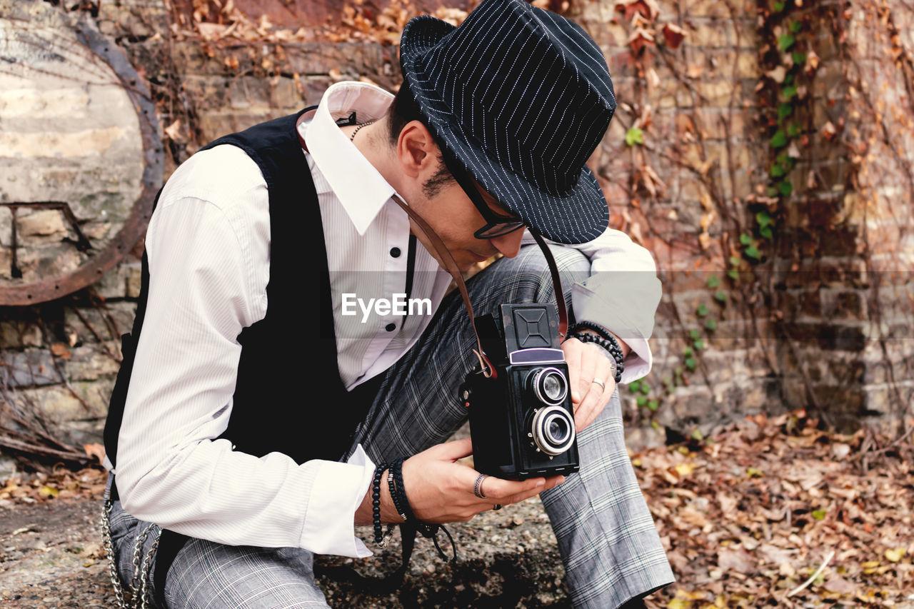 Male photographer using vintage medium format photo camera.