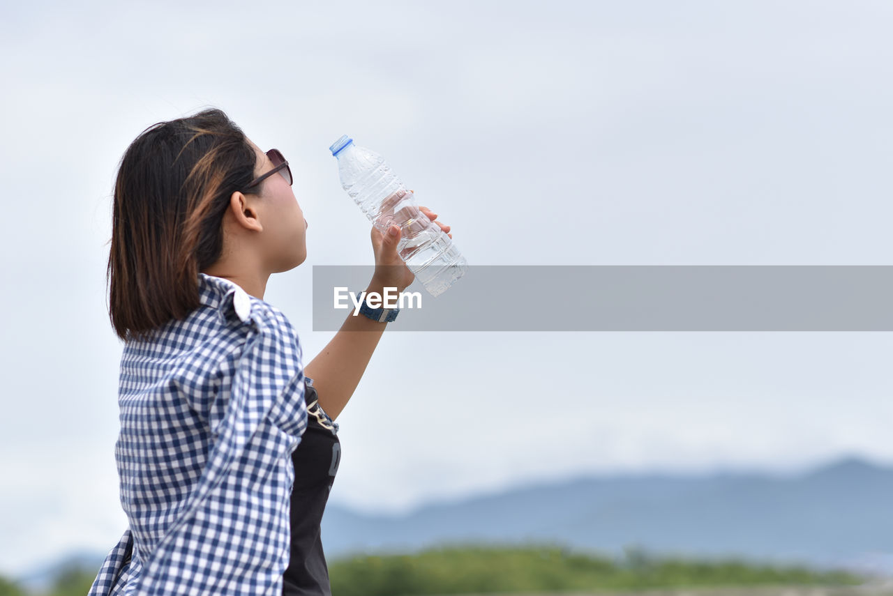 Side view of woman drinking water from bottle against sky