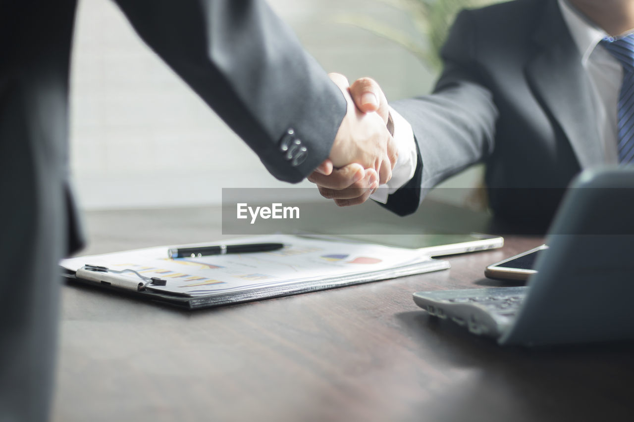 business, table, communication, business person, businessman, wireless technology, cooperation, connection, selective focus, midsection, laptop, men, office, working, technology, computer, corporate business, teamwork, well-dressed, indoors, using laptop, coworker, formal businesswear, handshake