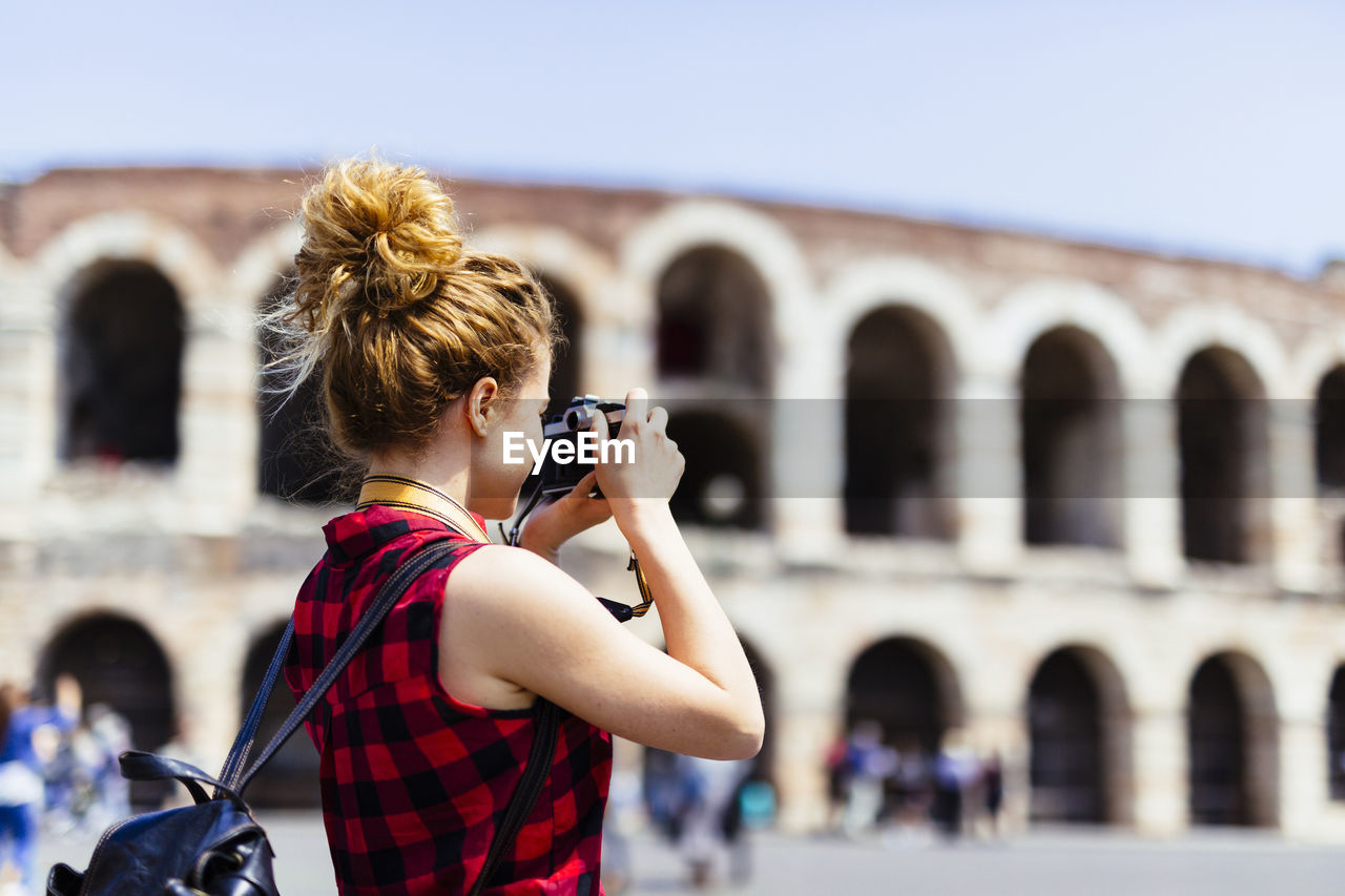 WOMAN PHOTOGRAPHING AGAINST BUILT STRUCTURE WITH CAMERA