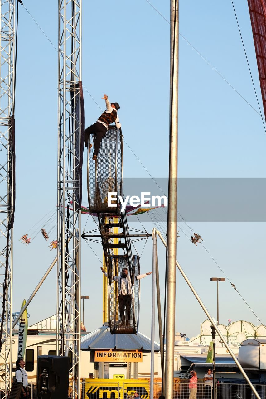 day, clear sky, low angle view, transportation, outdoors, real people, mode of transport, sky, nautical vessel, mast, built structure, men, architecture, one person, people
