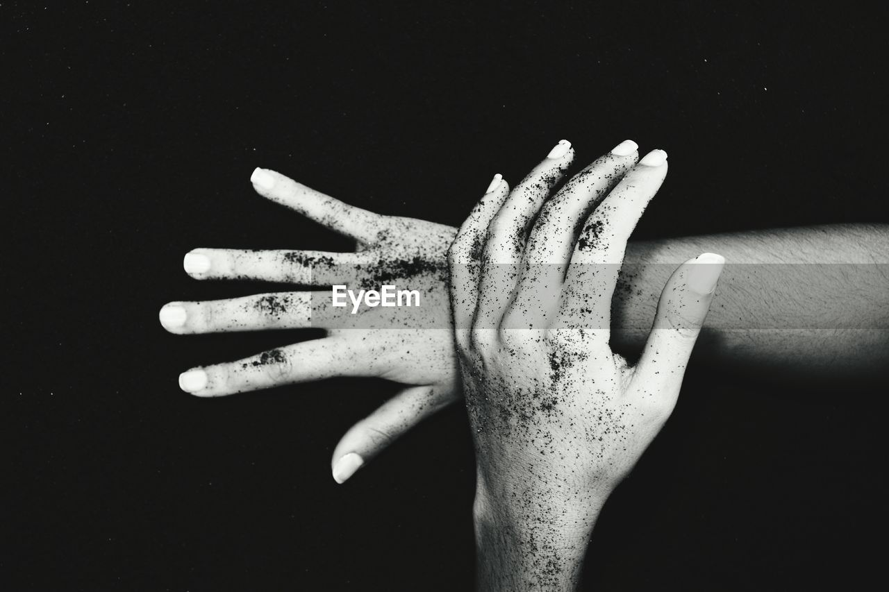 Cropped messy hands of woman against black sand