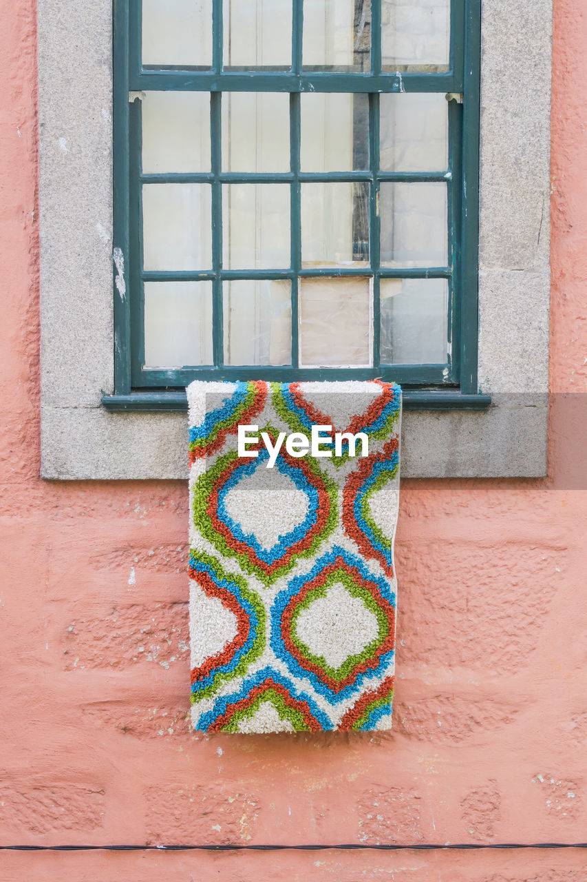 window, architecture, multi colored, built structure, building exterior, day, no people, wall - building feature, pattern, building, textile, close-up, house, outdoors, glass - material, wool, brick, wall, green color, window sill
