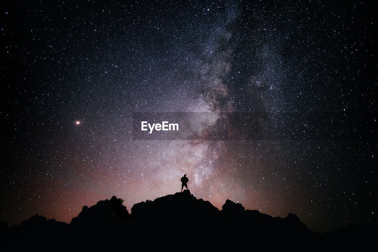A person standing looking at the star field and the milky way