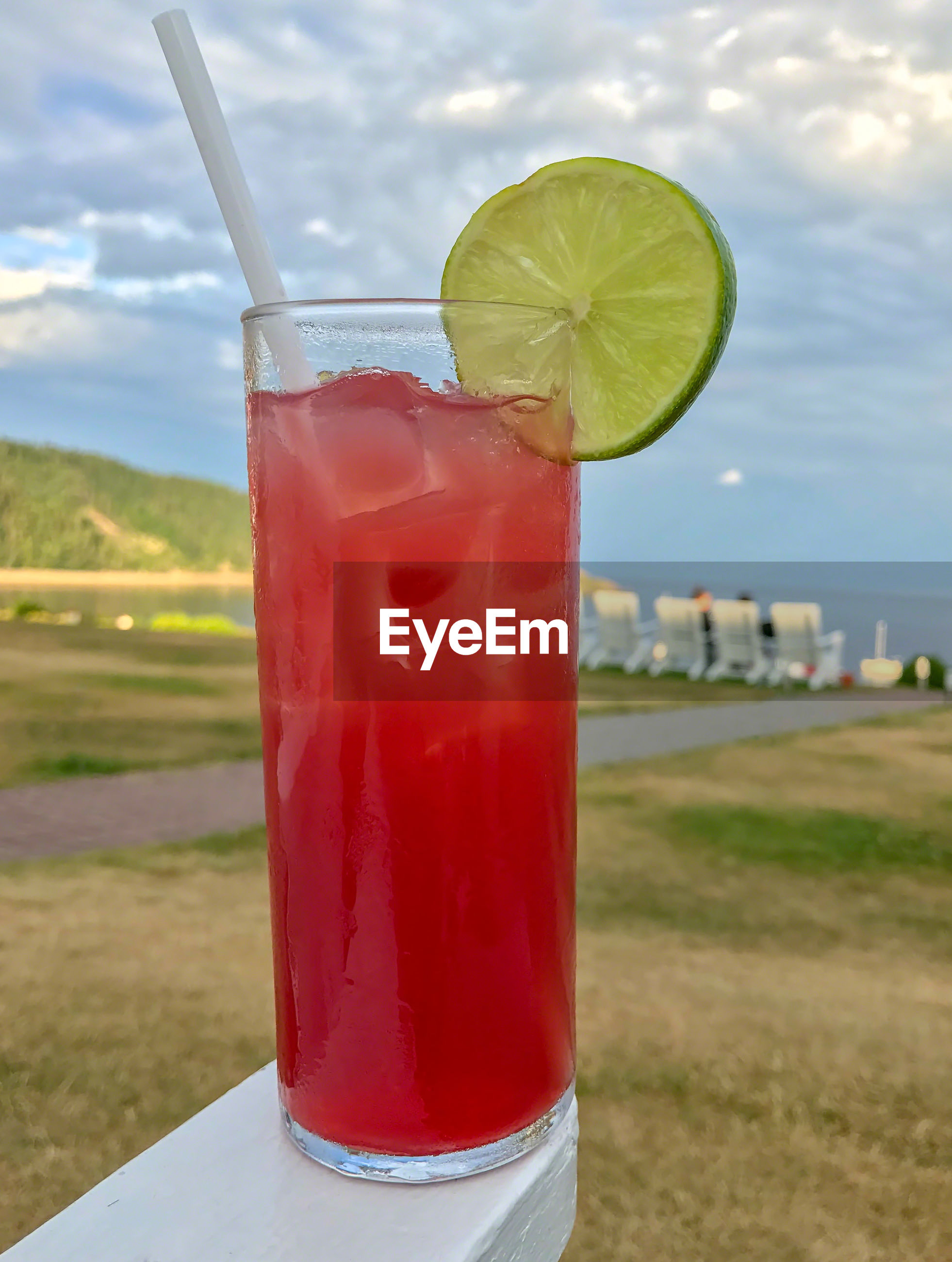 CLOSE-UP OF DRINK ON RED AGAINST SKY