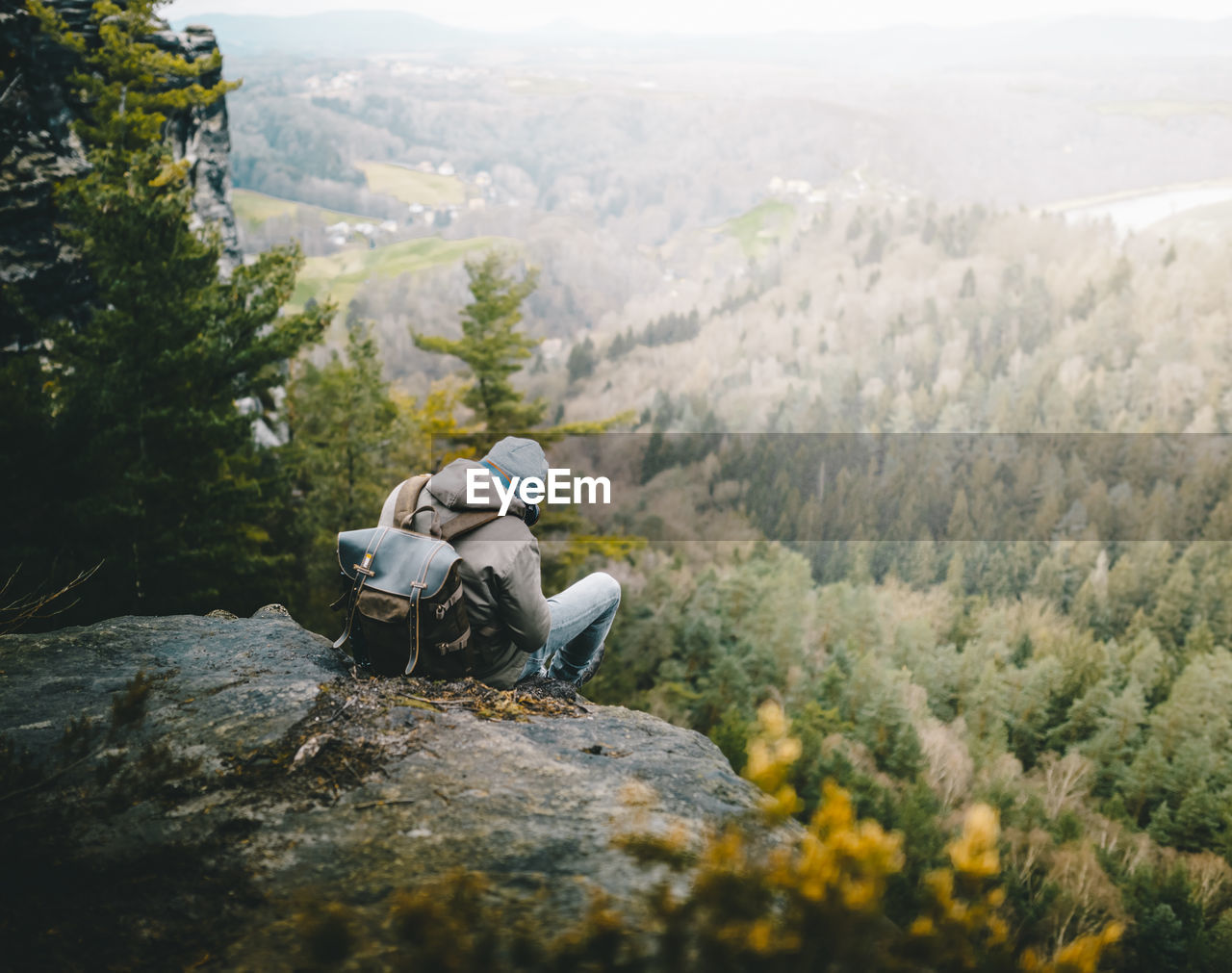 Rear View Of Hiker Sitting On Rock Looking At Trees