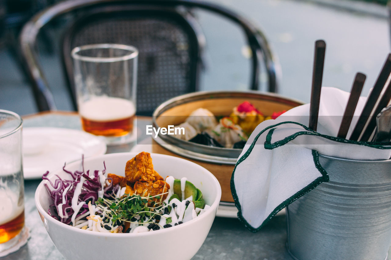 Pan-asian food - different dim sums in a bamboo bowl and salad. lunch for two with beer