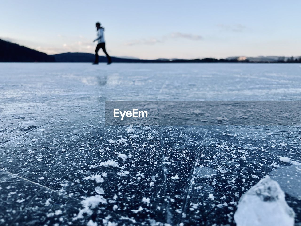 Woman walking on frozen lake against sky during winter