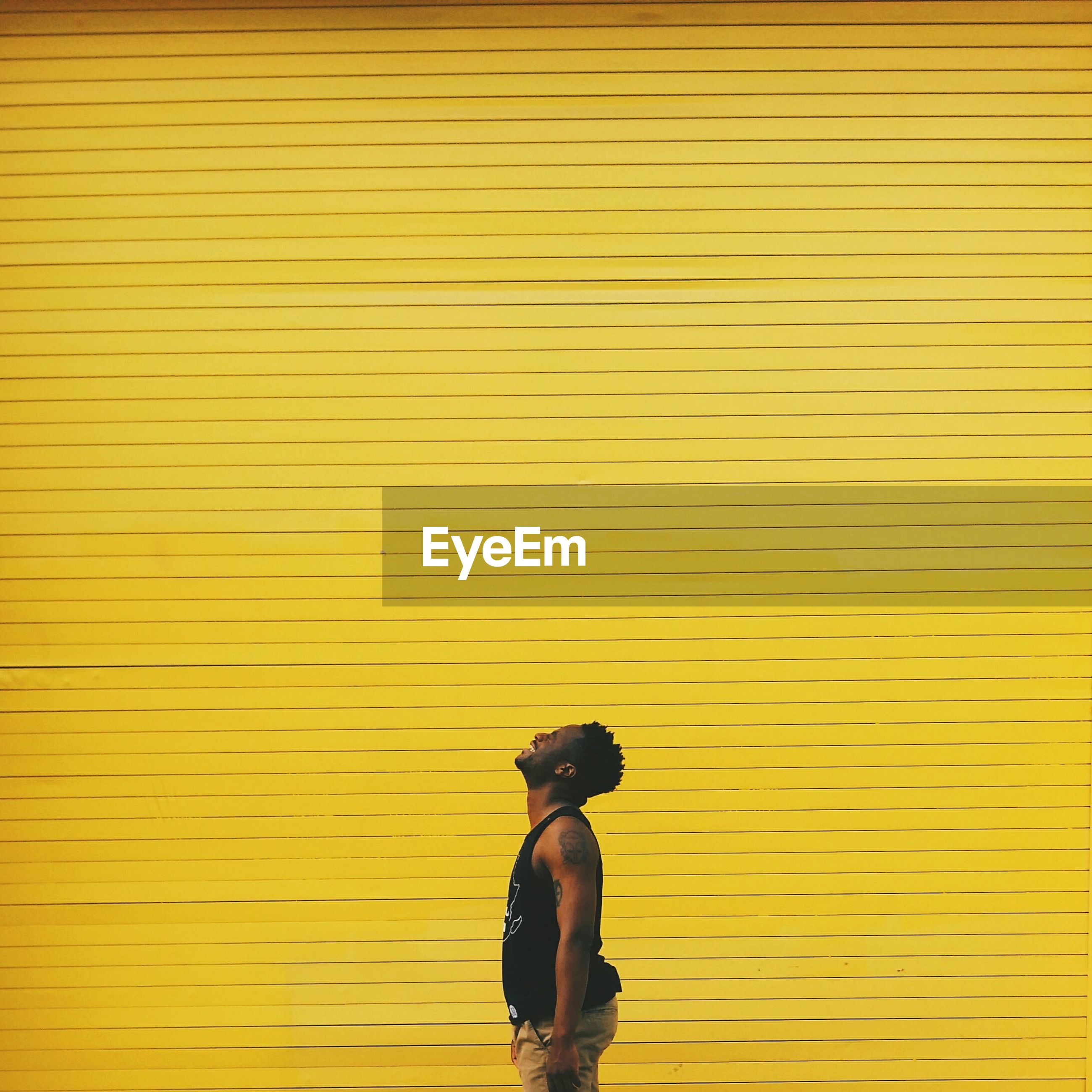 Man standing against yellow shutter
