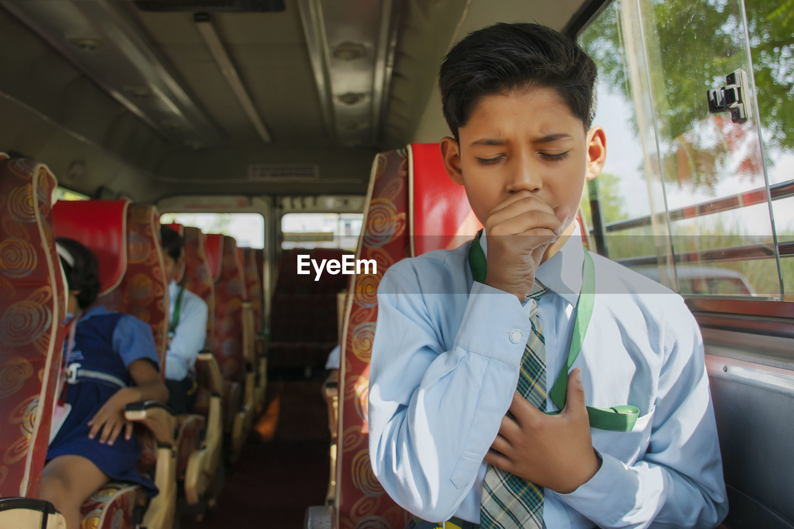 Indian boy coughing in school bus, air pollution, virus