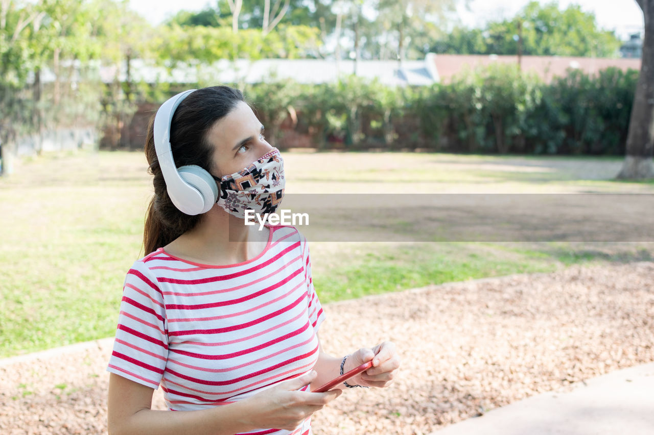 Woman wearing mask looking up whiles standing in park