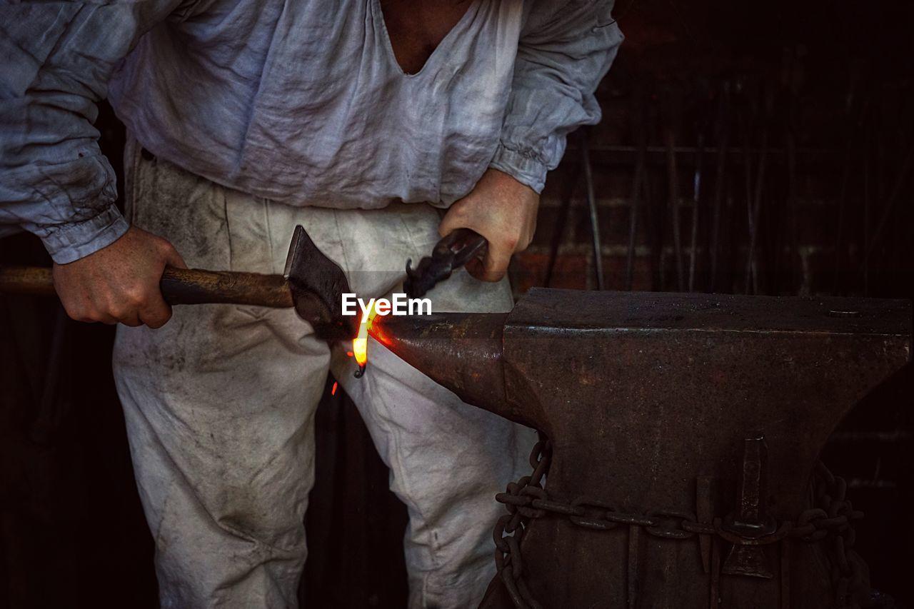 Midsection Of Blacksmith Using Hammer On Anvil At Workshop