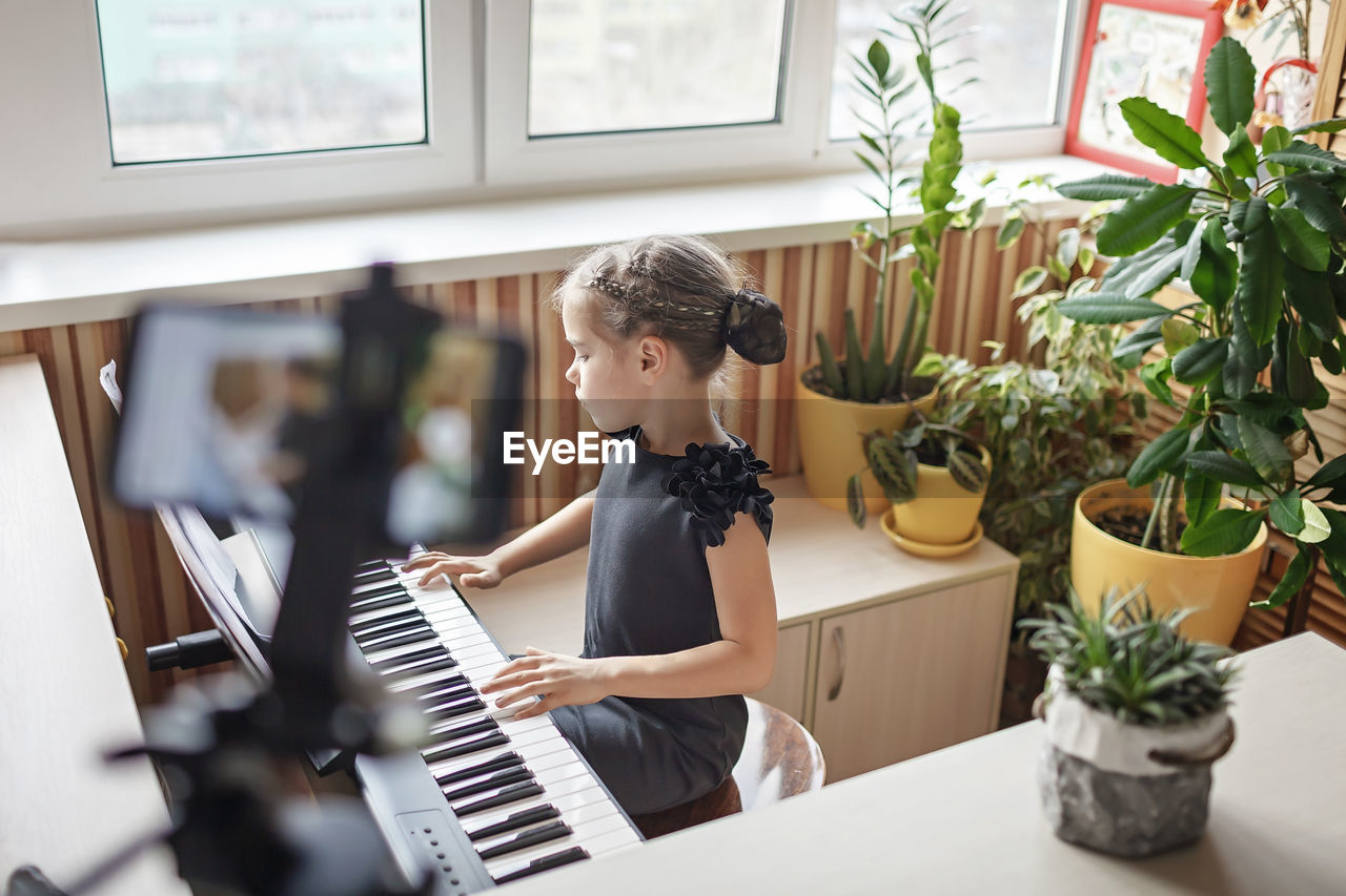 Side view of boy playing piano at home