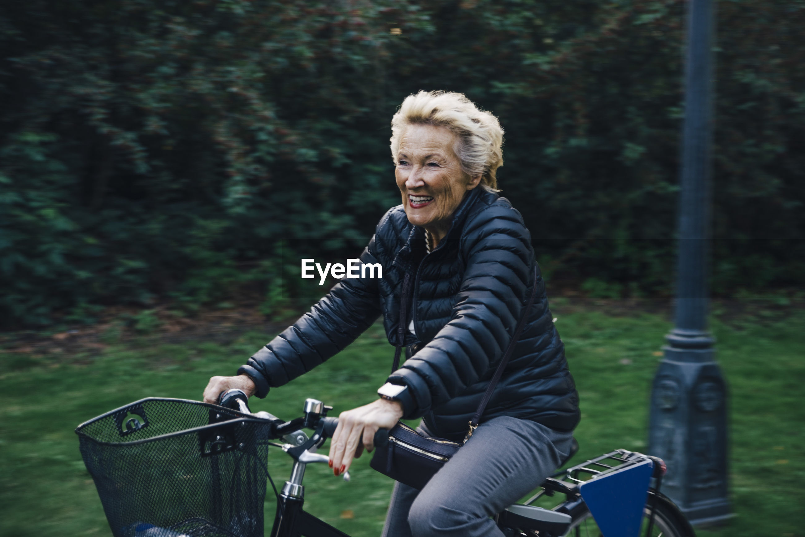 Smiling senior woman riding bicycle in park