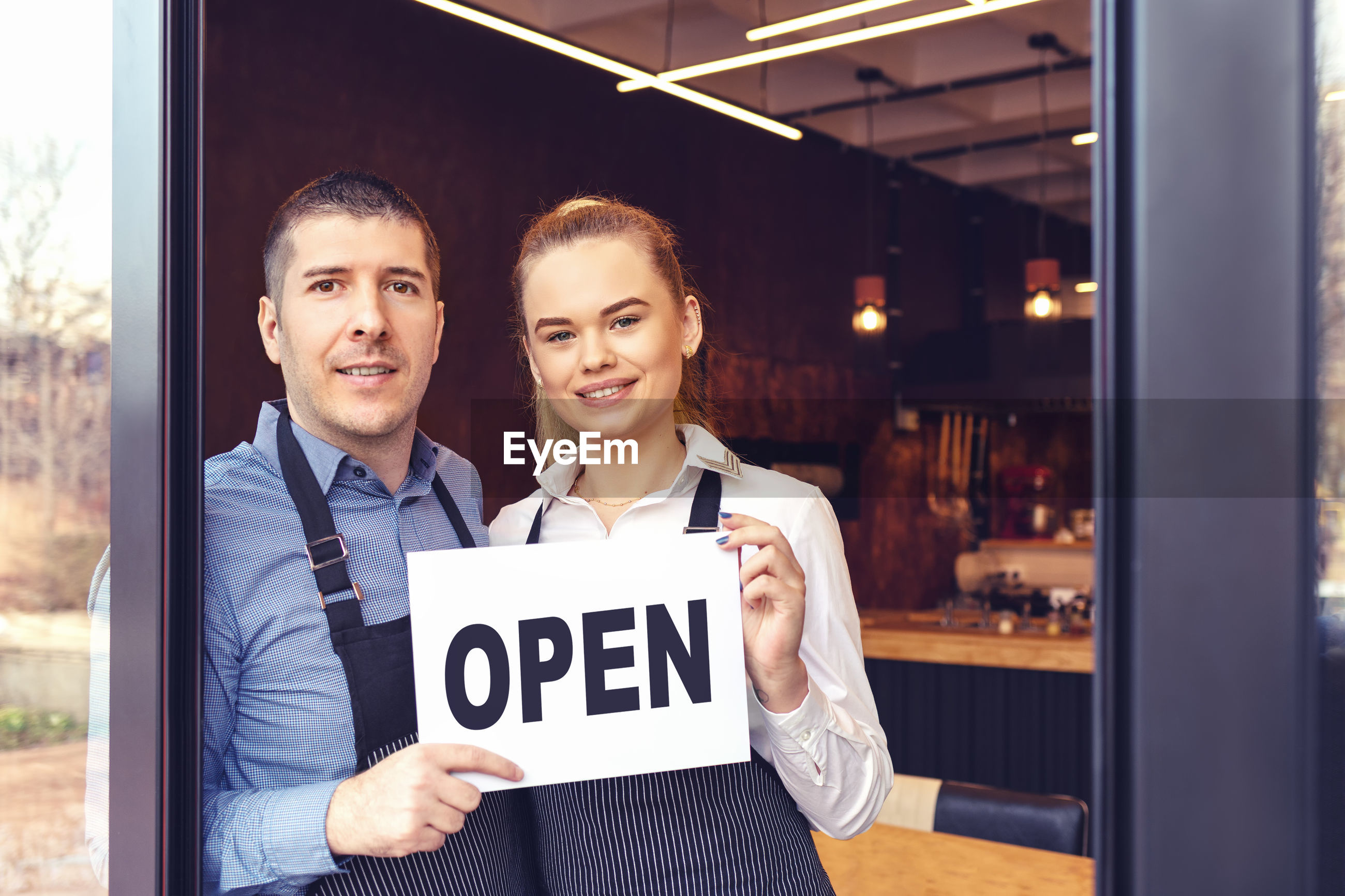Portrait of smiling coworkers holding open sign in restaurant