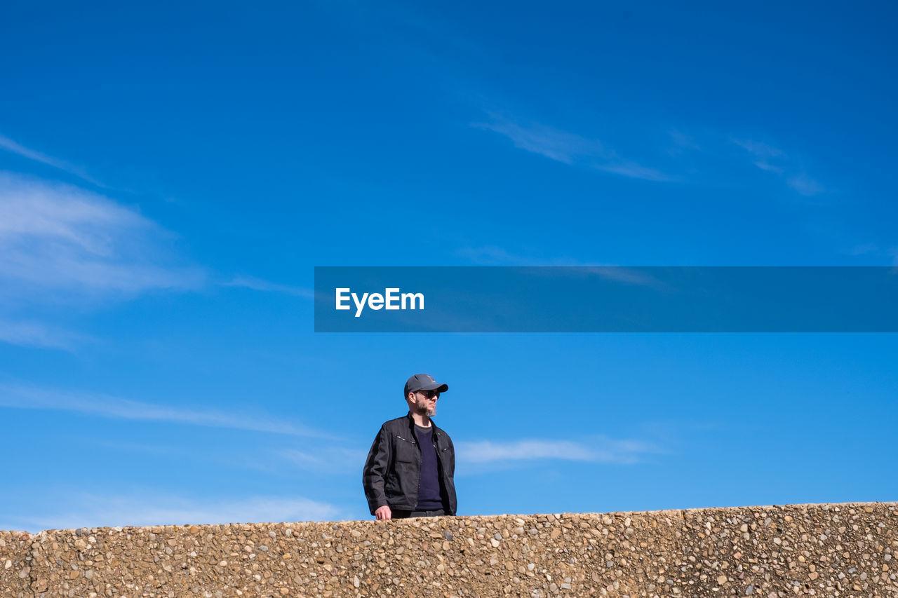 Man Standing Against Blue Sky