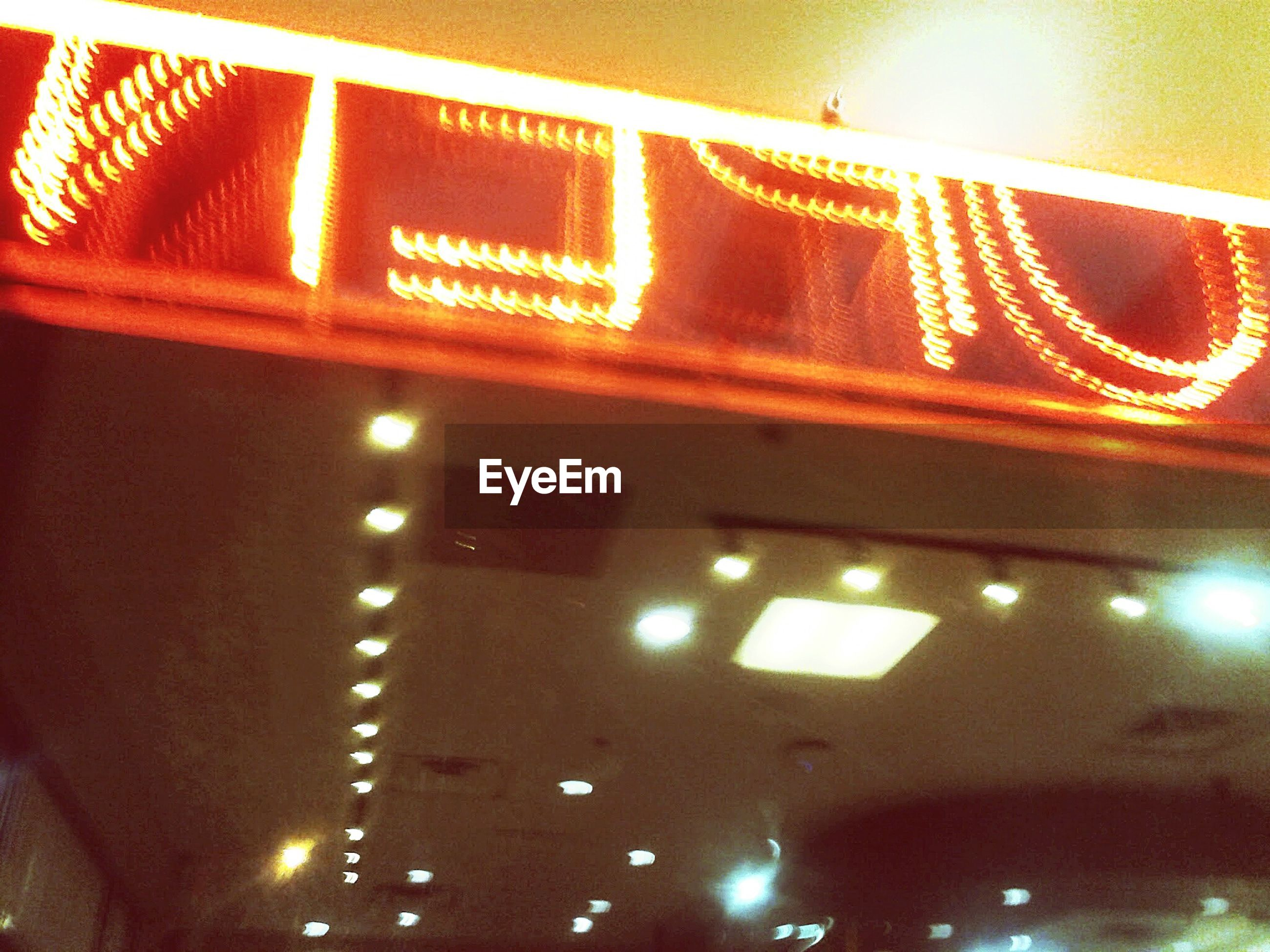 Low angle view of illuminated open sign on ceiling