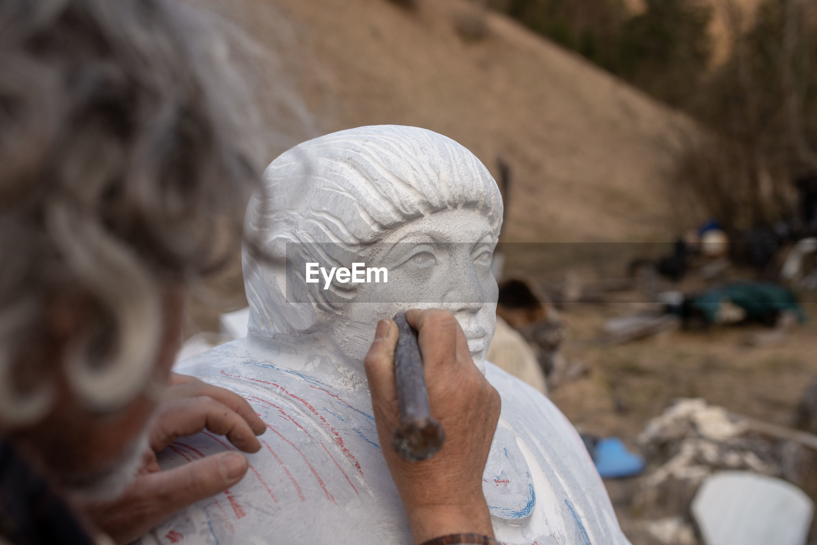 CLOSE-UP OF WOMAN HOLDING SCULPTURE