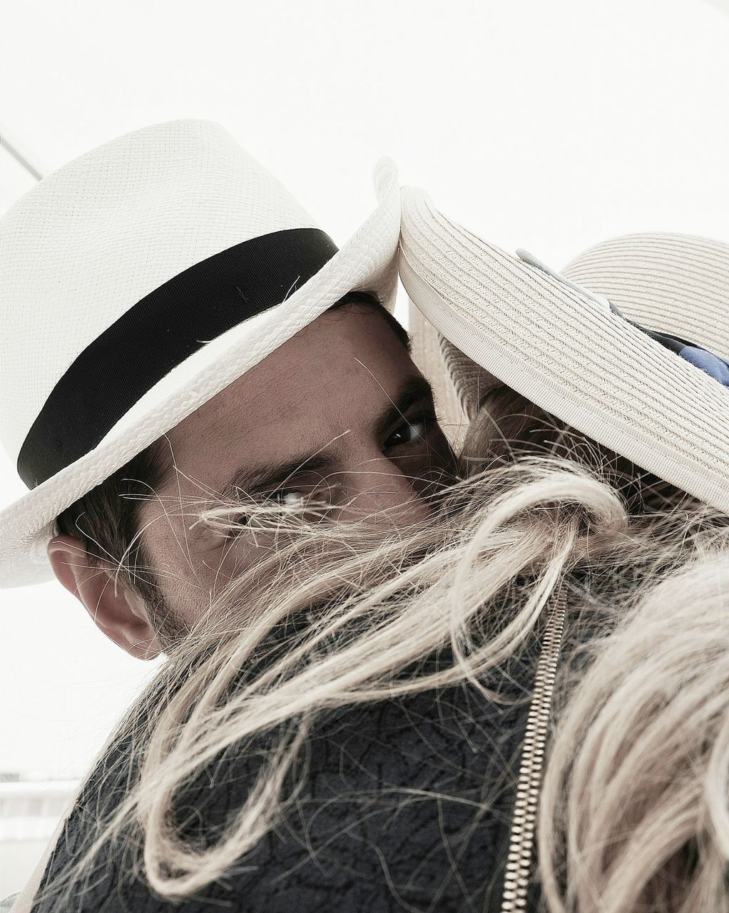 Low angle view of couple embracing against clear sky