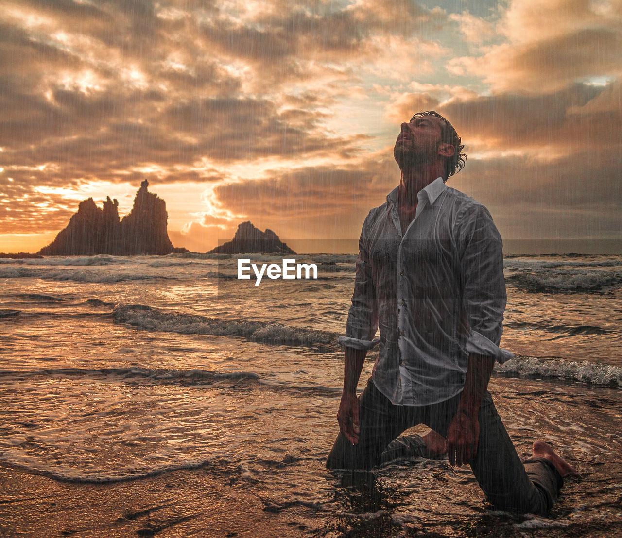 Man kneeling on beach against sky during sunset