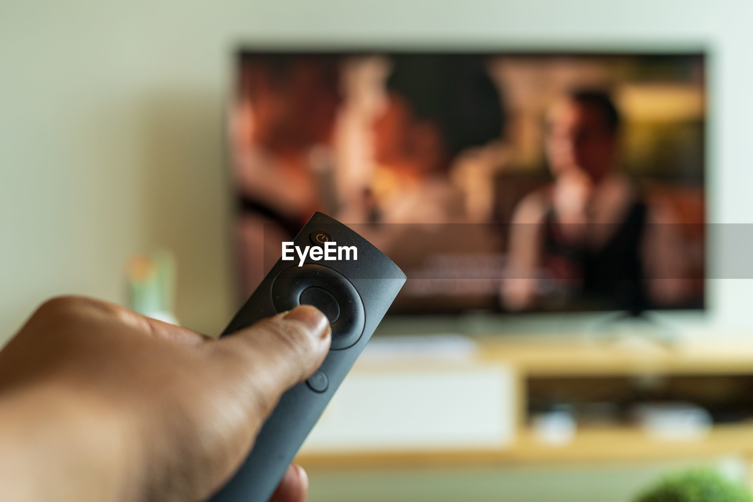 Cropped hand of person holding remote control while watching tv