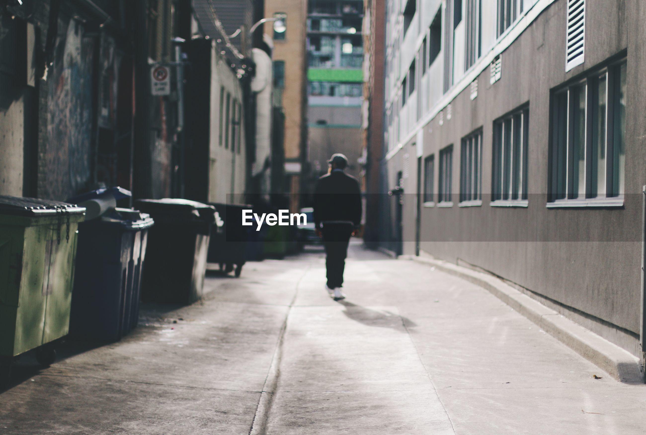 Man walking in empty alley