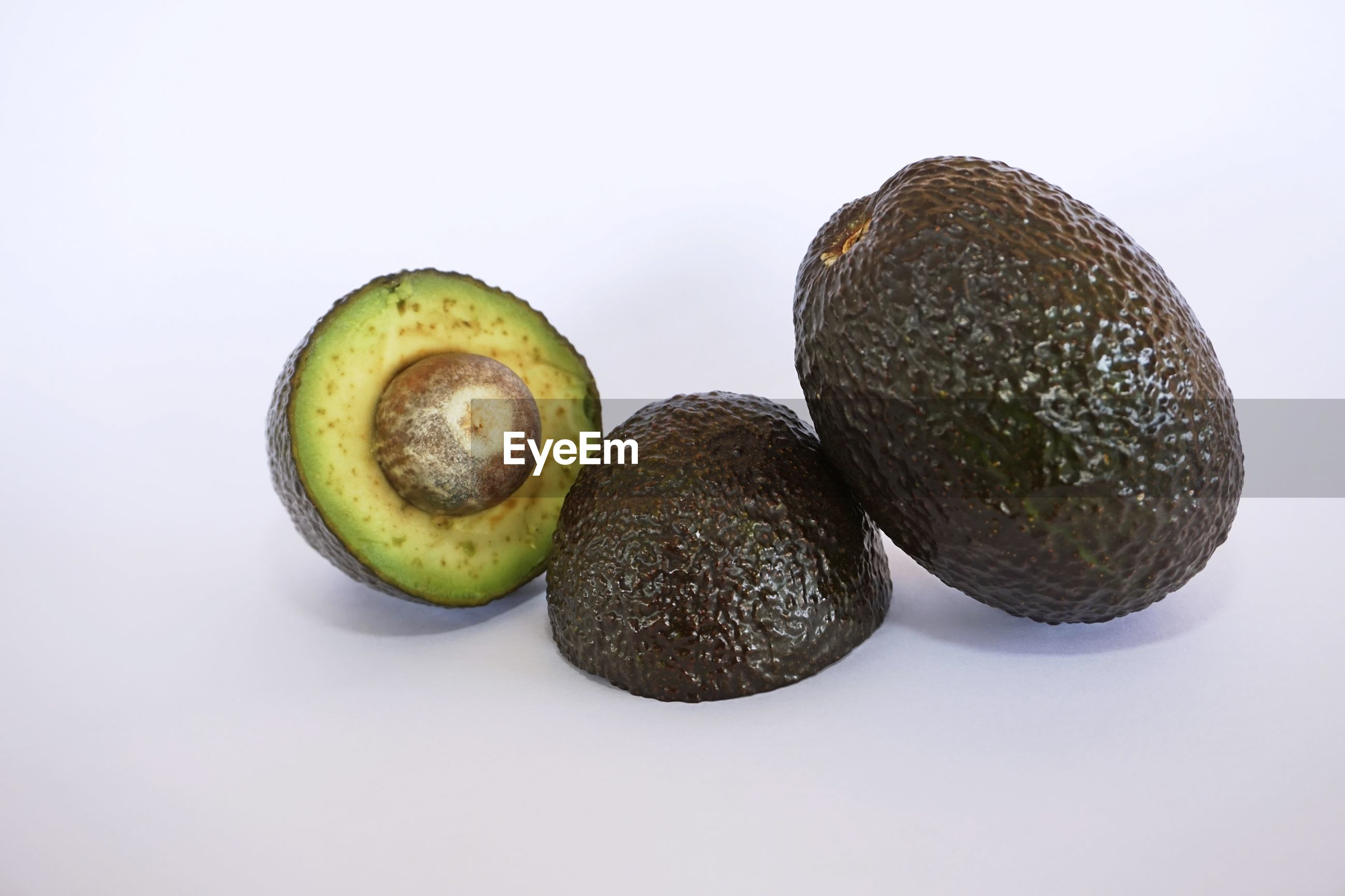 Close-up of avocado fruits against white background