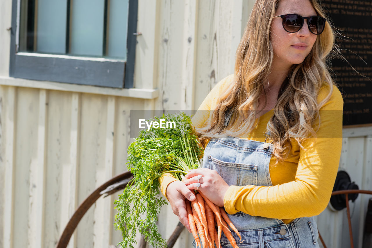 Beautiful woman holding carrots while standing outdoors