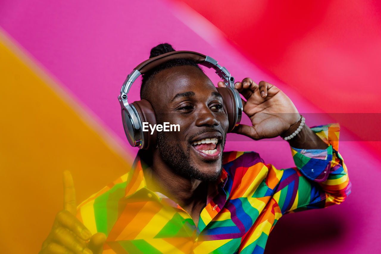 Smiling man listening music against colored background