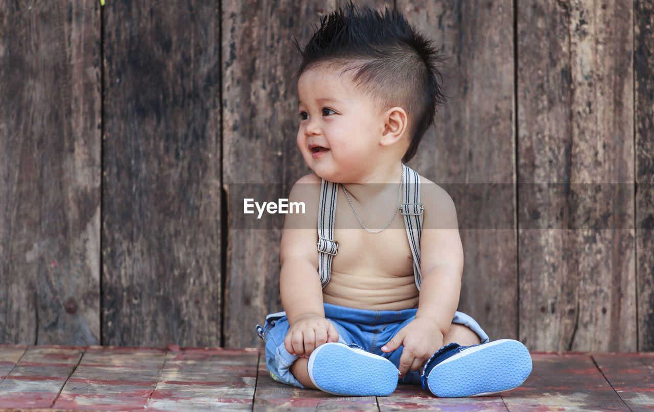 Cute baby boy against on wooden table
