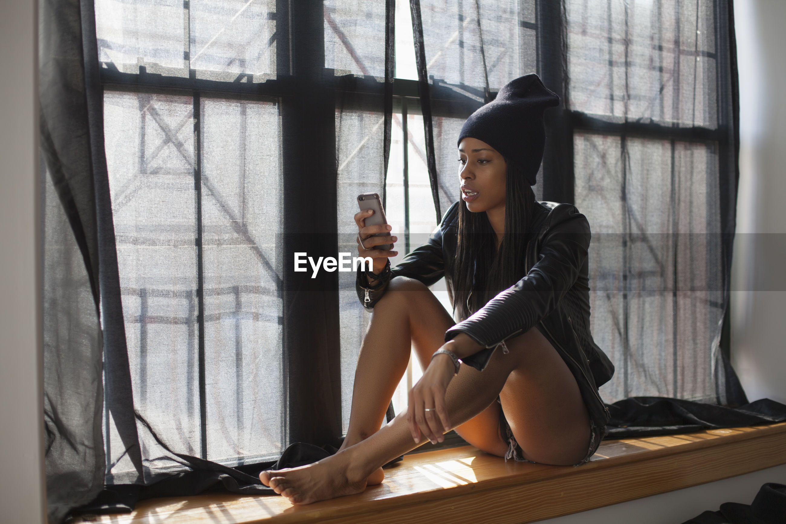 WOMAN LOOKING AT WINDOW AT HOME