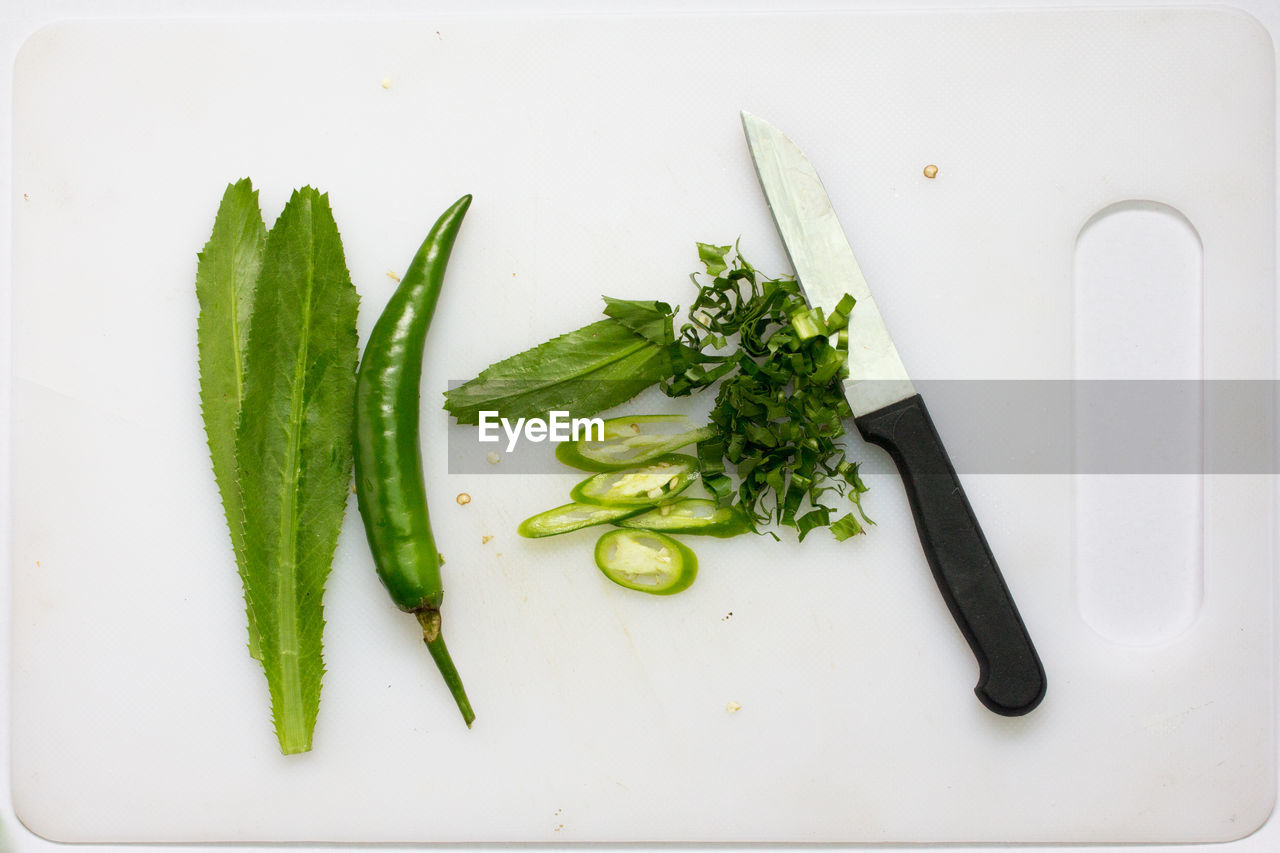 Close-Up Of Green Chili Peppers And Knife Against White Background